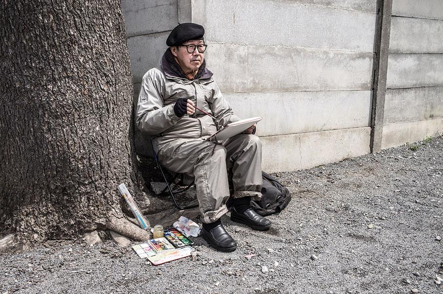 Älterer Mann mit Pinsel und Block sitzend im Ueno-Koen Park in Tokyo, Japan als Farbphoto