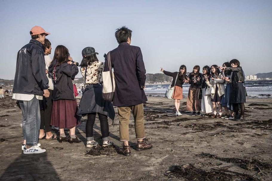 Schüler fotografieren sich gegenseitig auf dem Yuigahama Beach in Kamakura, Japan als Farbphoto