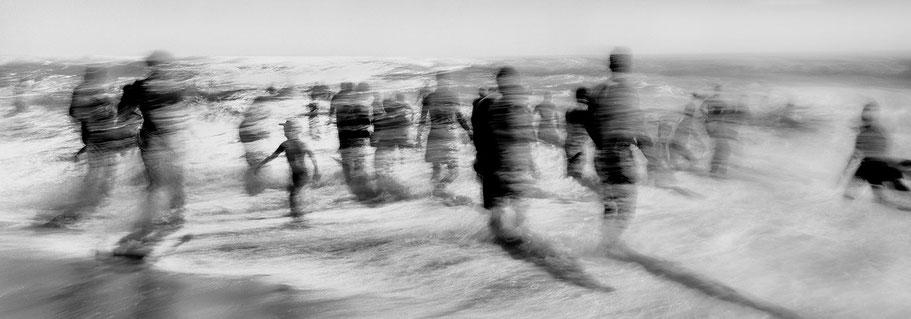 Menschen trotzen den Wellen des Atlantiks als schemenhafte Langzeitbelichtung in schwarz-weiß als Panorama-Photographie