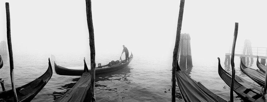Nebelstimmung mit Gondoliere nähe Molo San Marco, Venedig, als Schwarzweißphoto im Panorama-Format