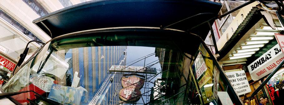 Spiegelung des Straßenlebens in Hongkong, China, als Farbphoto im Panorama-Format