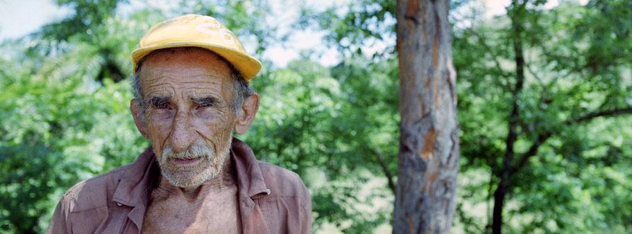 Alter Kubaner verkauft in Mayari Früchte an der Straße, Farbphoto als Panorama-Photographie