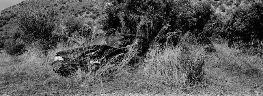 Altes Schrottauto bei Nea Itilo auf dem Peloponnes, Griechenland,  als Schwarzweißphoto im Panorama-Format