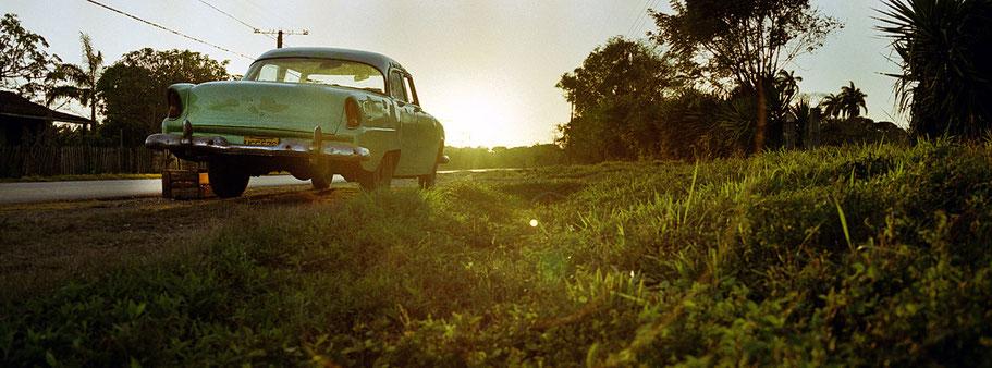 Grüner Oldtimer steht an der Straße nähe Caibarien als Farbphoto im Panoramaformat, Cuba