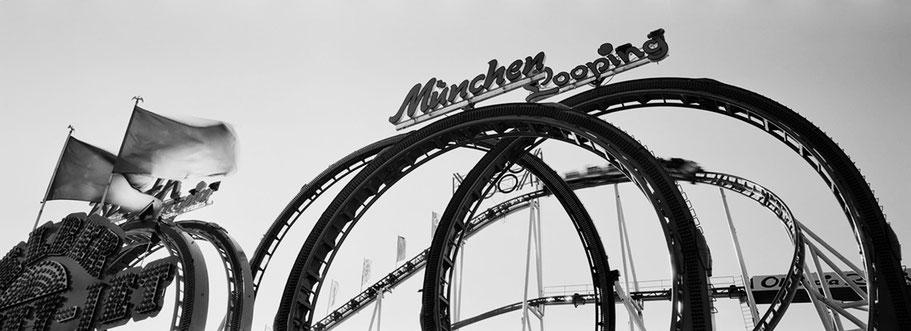 """Bild des Fahrgeschäfts """"München Looping"""" auf dem Oktoberfest in München als Schwarzweißphoto im Panorama-Format"""