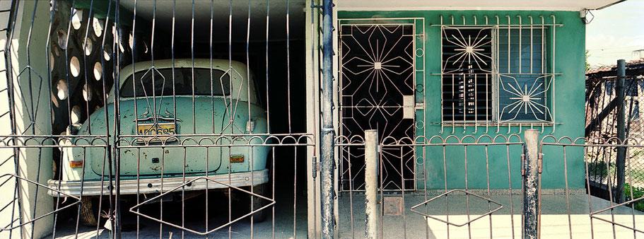 Grüner Oldtimer steht vor einem Haus in der Garage in Camagüey  als Farbphoto im Panoramaformat, Cuba