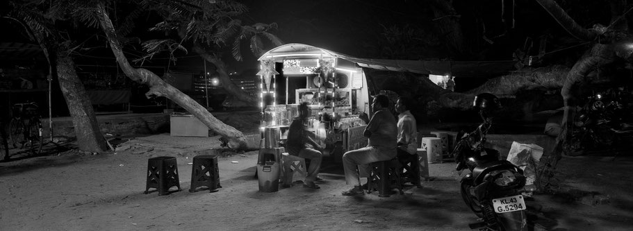 Nachtszene mit Männern auf dem Vasco Da Gama Square in Fort Kochi , Indien, in schwarz-weiß als Panorama-Photographie