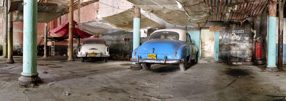 Blauer und weißer Oldtimer stehen in der Garage in der Altstadt von Havanna  als Farbphoto im Panoramaformat, Cuba