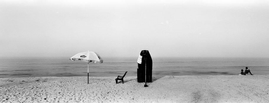 Vater und Sohn sitzen frühmorgens am leeren Strand von Marari Beach, Indien, in schwarz-weiß als Panorama-Photographie