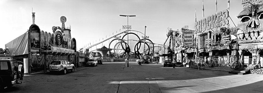 Bild der Fahrgeschäfte früh morgens auf dem Oktoberfest in München als Schwarzweißphoto im Panorama-Format
