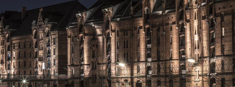 Speicherstadt-Fassaden by night am Zollhafen in Hamburg als Farbphoto im Panorama-Format