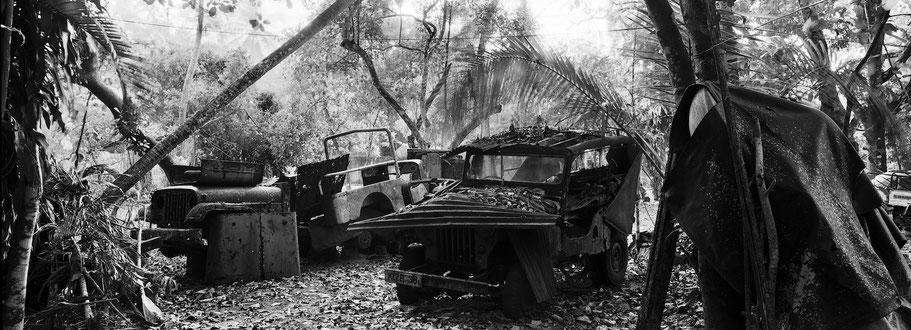 Reste von Oldtimer-Jeeps bei Marari in Kerala , Indien, als Schwarzweißphoto im Panorama-Format