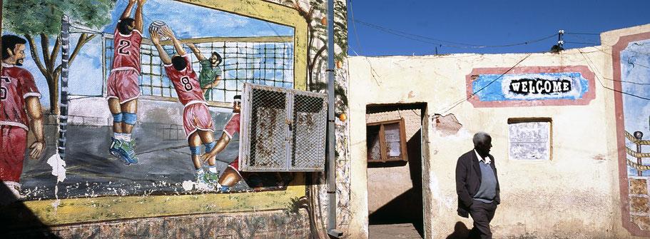 Eingang zum Basketballfeld mit Mann in Asmara, Eritrea, als Farbphoto im Panorama-Format