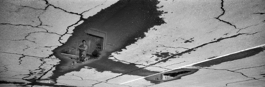 Spiegelung auf der Straße in den Kunst-Studios in Pyongyang, Nord Korea, als Schwarzweißphoto im Panorama-Format