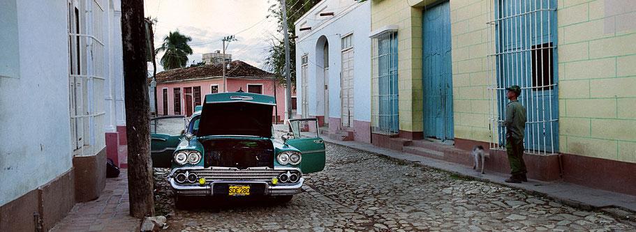 Grüner Oldtimer mit Motorpanne  steht in den Straßen von Trinidad de Cuba  als Farbphoto im Panoramaformat, Cuba