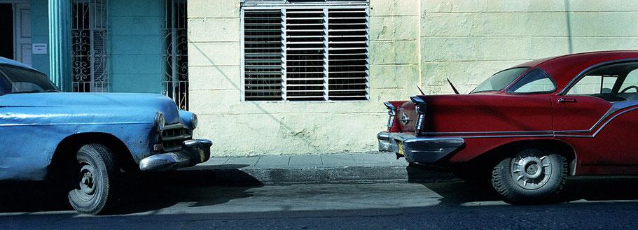 Roter und blauer Oldtimer auf der Straße in Santa Clara als Farbphoto im Panoramaformat, Cuba