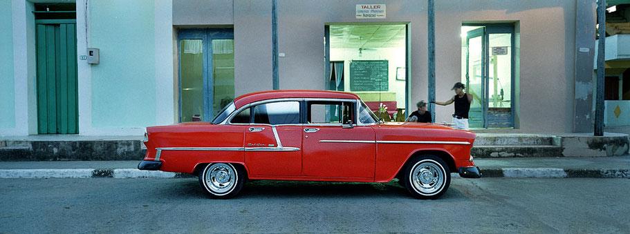 Roter Oldtimer steht vor Laden in Baracoa als Farbphoto im Panoramaformat, Cuba