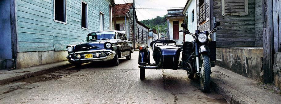 Schwarzer Oldtimer und Motorrad auf der Straße in Baracoa als Farbphoto im Panoramaformat, Cuba