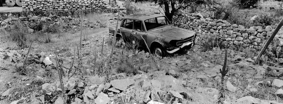 Alter Fiat in Areopoli auf dem Peloponnes, Griechenland,  als Schwarzweißphoto im Panorama-Format