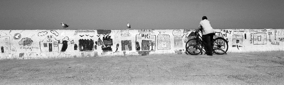 Mann mit Fahrrad vor einer Wand im Hafen von Essaouira in Marokko in schwarz-weiß als Panorama-Photographie