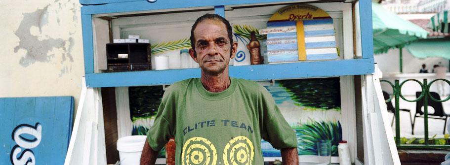 Kubaner  in Manzanillo steht vor einem Kiosk, Farbphoto als Panorama-Photographie