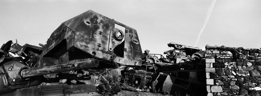 Kriegsschrott aufgetürmt als Mauer im Tank Graveyard in Asmara, Eritrea, als Schwarzweißphoto im Panorama-Format