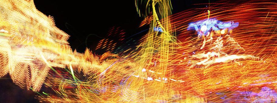 Nächtliche Aufnahme von Lichtspuren der Fahrgeschäfte auf dem Oktoberfest in München als Farbphoto im Panorama-Format