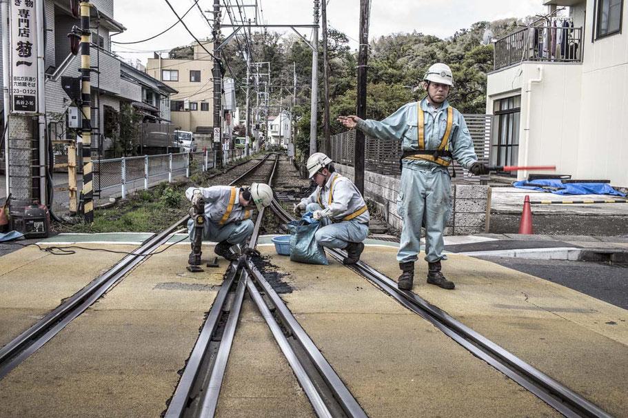 Drei Arbeiter bessern Bahnübergang in Kamakura, Japan aus als Farbphoto