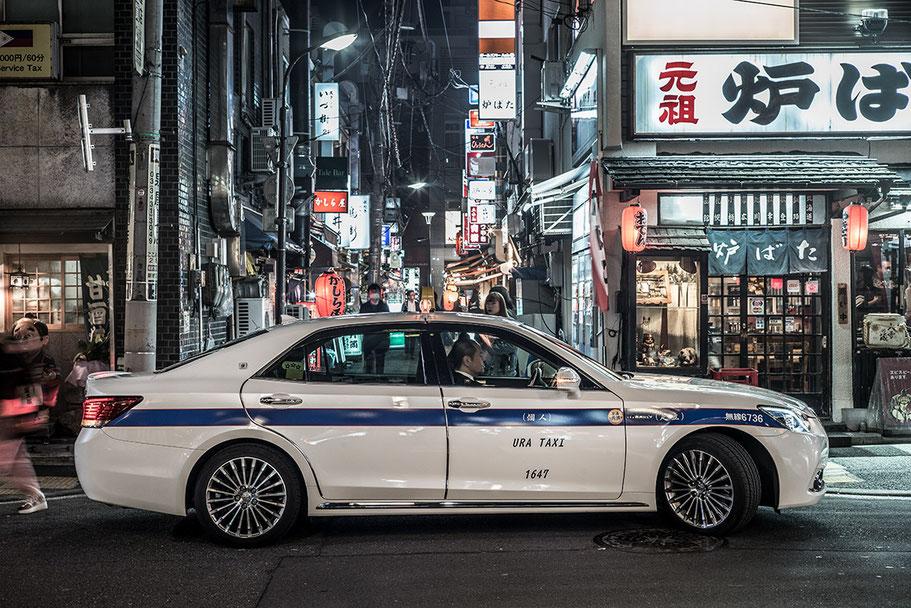 Nächtliche Straßenszene mit Taxi in Shimbashi in Tokyo, Japan als Farbphoto