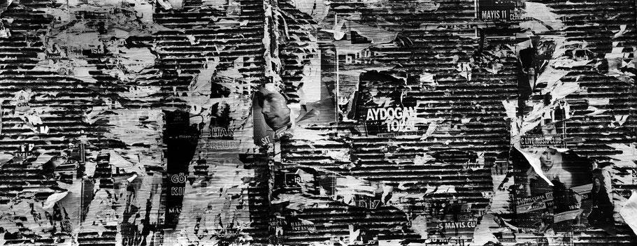 Reste von Plakaten an Häuserwand in Beyoglu in Istanbul, Türkei als Schwarzweißphoto im Panorama-Format