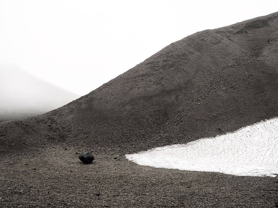 Landschaftsaufnahme von Vulkanasche und Schneefeld als Farb-Photographie, Island/Iceland