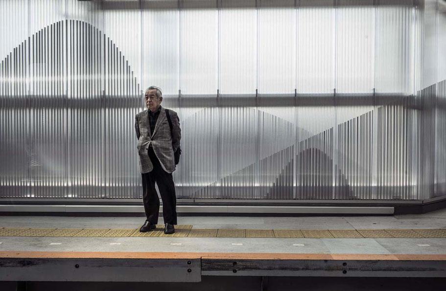 Älterer Mann steht auf dem Bahnsteig im Bahnhof von Ofuna, Japan als Farbphoto