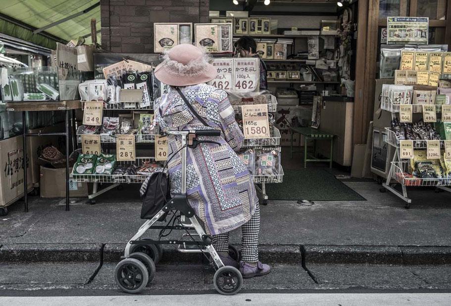 Ältere Frau sitzt auf Rollator vor einem Geschäft in Ofuna, Japan als Farbphoto