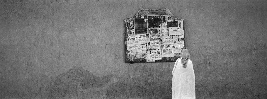 Alte Frau vor Wandzeitung in der Harnet Avenue in Asmara, Eritrea, als Schwarzweißphoto im Panorama-Format