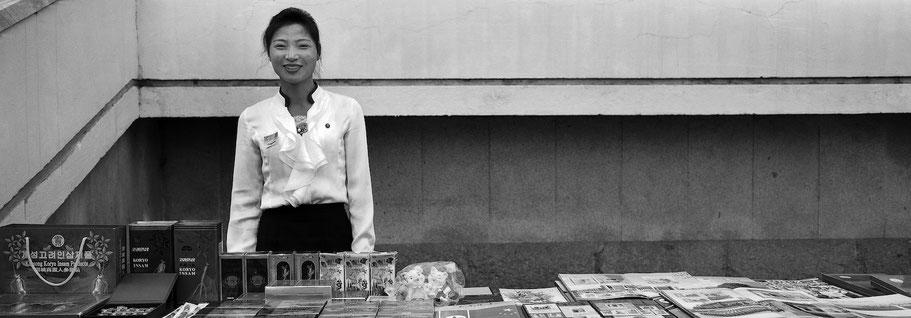 Junge Frau mit Verkaufstand auf der Autobahnraststätte Teahouse, Nord Korea,  in schwarz-weiß als Panorama-Photographie