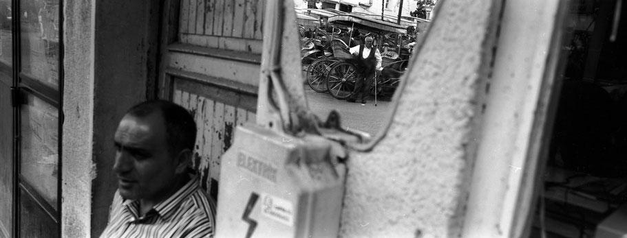 Spiegelung eines Kutschers auf der Büyükada Prinzesininsel in Istanbul, Türkei als Schwarzweißphoto im Panorama-Format