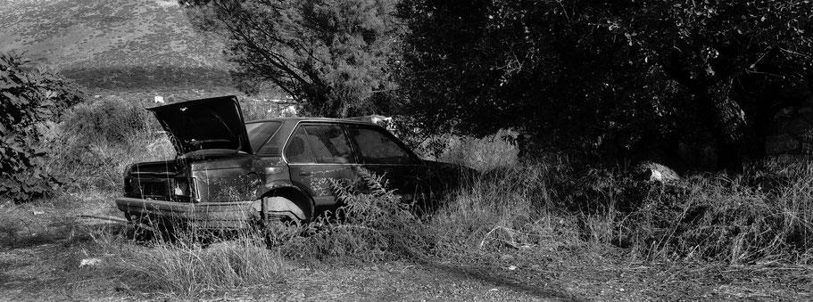 Alter Opel bei Areopoli auf dem Peloponnes, Griechenland,  als Schwarzweißphoto im Panorama-Format