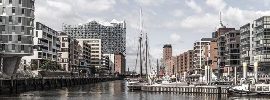 Blick auf die Elbphilharmonie vom Sandtorhafen in Hamburg als Farbphoto im Panorama-Format.