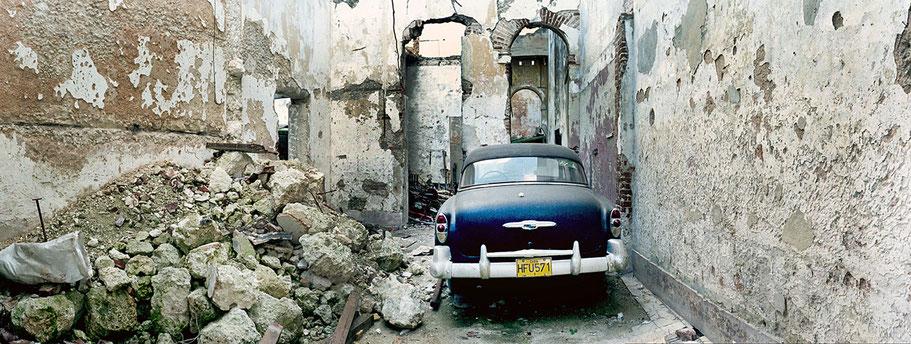 Oldtimer im Hinterhof in der Altstadt von Havanna als Farbphoto im Panoramaformat, Cuba