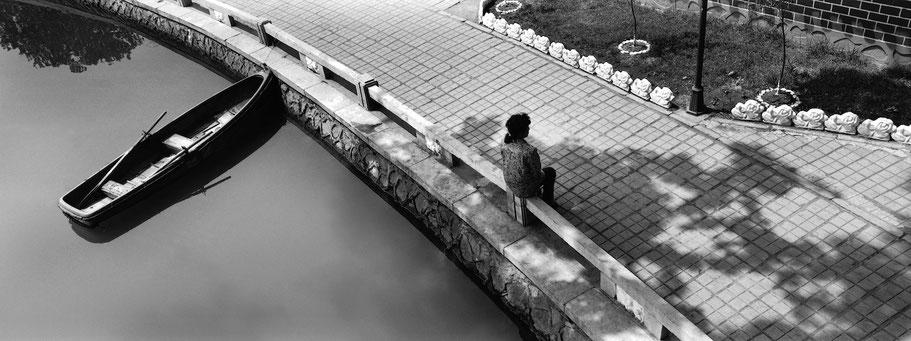 Frau sitzt einsam an einem Teich in Sariwon, Nord Korea,  in schwarz-weiß als Panorama-Photographie