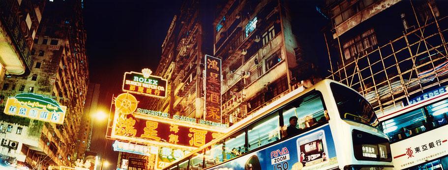 Abendaufnahme im bunten Häusermeer von Hongkong, China, als Farbphoto im Panorama-Format