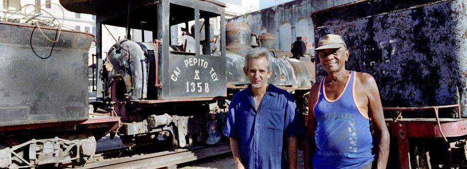 Zwei Kubaner in Havanna posieren vor alten Lokomotiven, Farbphoto als Panorama-Photographie