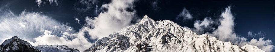 Landschaftsaufnahme der verschneiten Alpen in Samnaun, Schweiz als Panorama-Photographie in Color