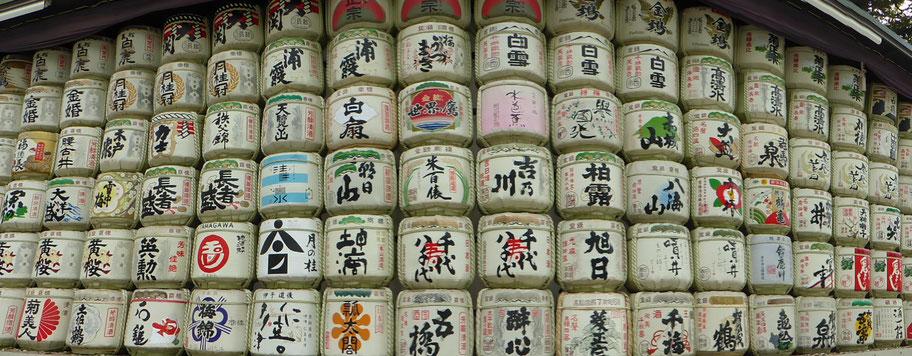 Auf dem Weg zum riesigen Shinto-Tor vom Meiji Schrein stehen von japanischen Sake-Brauereien gespendete bunte Sake-Fässer.