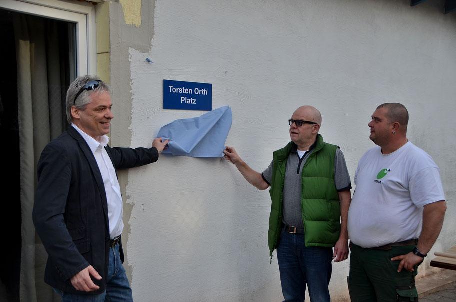 Unser Bürgermeister Thomas Leis und unser 1. Vorsitzender Walter Weiland enthüllen das Namensschild des Erbauers. Rechts Torsten Orth, der in vielen Stunden seiner Freizeit den neuen Platz vor unserem Clubheim gebaut hat.