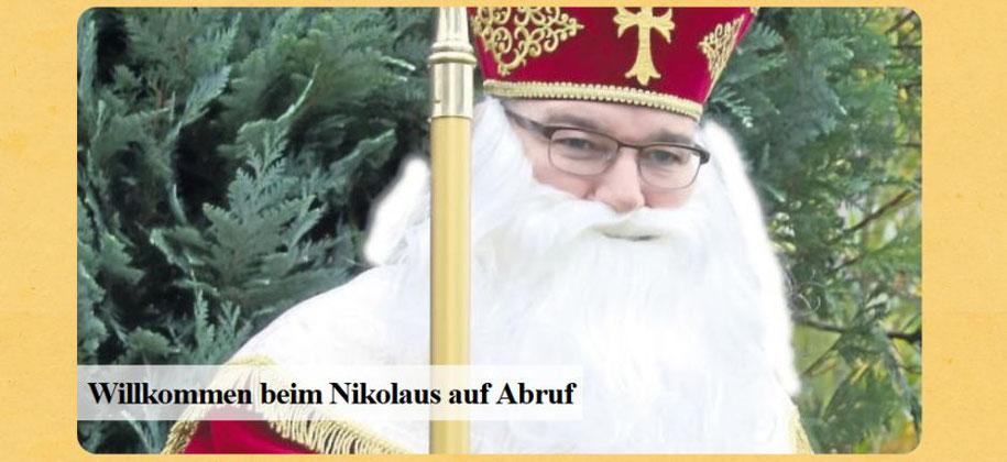 Ein Nikolaus mit Mitra und Bischofsstab steht vor einem grünen Busch. (Foto: nikolausev.de)