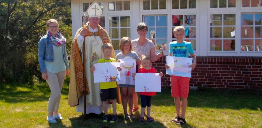 Der heilige Nikolaus und Pastoralreferentin sowie  Insel-Seelsorgerin Susanne Wübker umrahmt von Kindern, die selbstgemalte Bilder in der Hand halten.