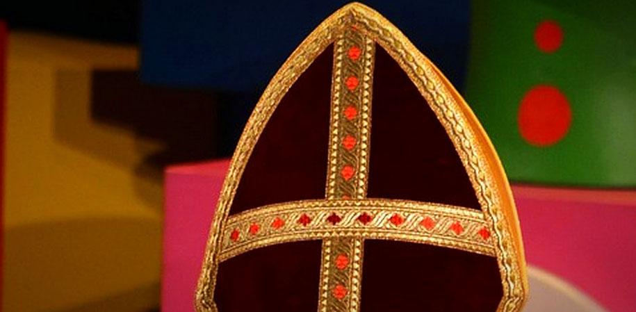 Vor pink-grünem Hintergrund ist eine rote Mitra mit goldenem Rand zu sehen. (Foto: pixabay)