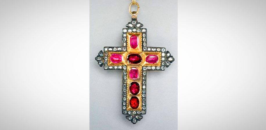 Ein Kreuz mit roten und rosa Steinen besetzt