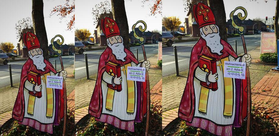 Ein lebensgroßer Nikolausaufsteller mit Bischofsstab und Mitra steht vor einem Baum am Straßenrand und weist den Weg zum Weihnachtsmarkt in Beelen.